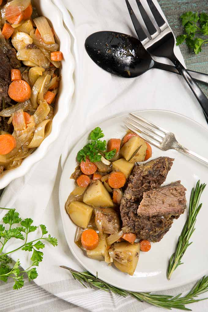 Top down view of a platter full of homemade pot roast with potatoes and carrots. A plate full of the meal sites to the lower right. Both containers are on a white table cloth and garnished with various fresh herbs.