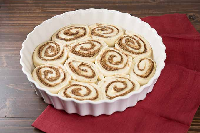 A round fluted white ceramic baking dish filled with dough rolled and cut to form the shape of cinnamon buns, read to go in the oven, on a brown tabletop covered partially with a red cloth.
