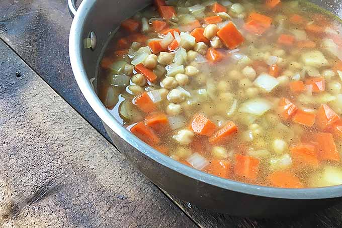 A pot of broth with beans, carrots, and onions | Foodal.com