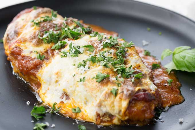 Oblique view of a chicken Parmesan dishi sitting in cast iron pan | Foodal