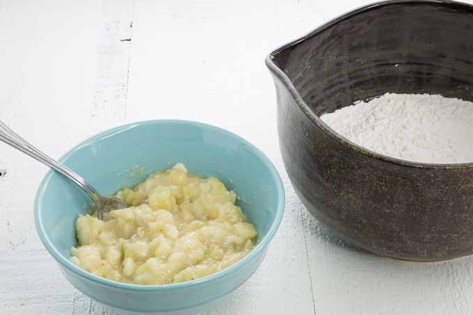 A small blue bowl of mashed bananas and a large gray pitcher of flour on a white surface.