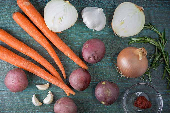 A blue-gray wooden surface topped with four carrots, one halved and one whole yellow onion, a head of garlic and several scattered cloves garlic, four red-skinned potatoes, and a small glass dish of tomato paste.