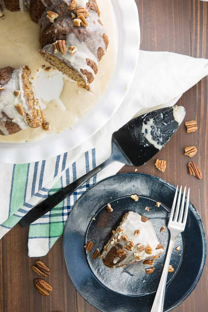 Top down view of a slice of banana cake on a black saucer and the remainder of the cake on white porcelain serving tray. A cake server and pecan pieces litter the table.