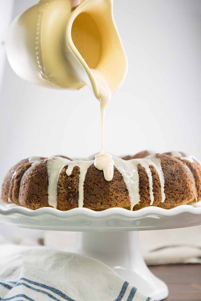 A banana cake on white porcelain cake stand with maple glaze being poured on vita a yellow porcelain serving pitcher.