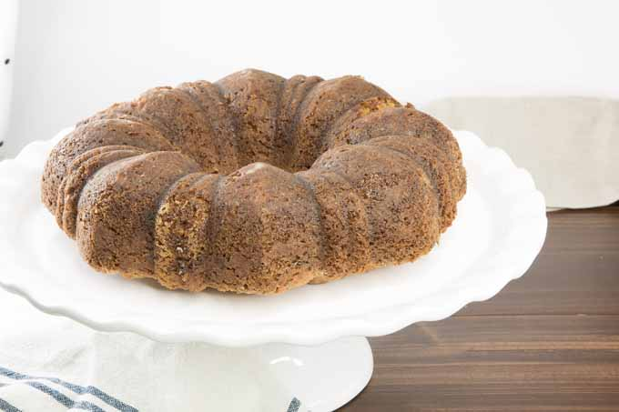 A brown bundt cake on a white cake stand, on a brown table with a white background.