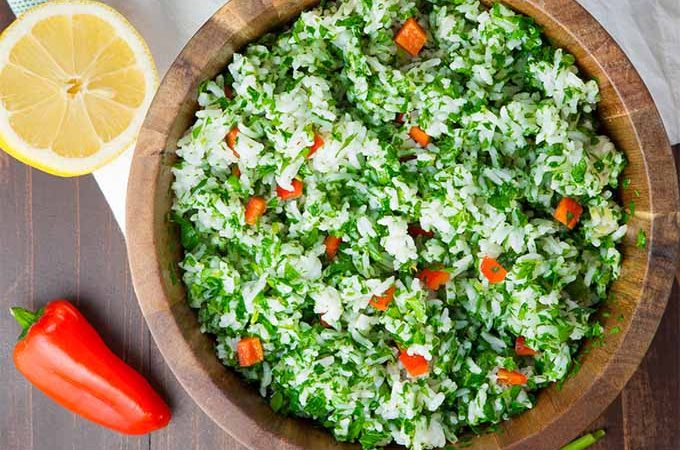 Top-down view of a white rice salad topped with minced parsley and red chopped bell pepper, on a brown wooden surface topped with a white cloth, with a mini bell pepper and half of a lemon.