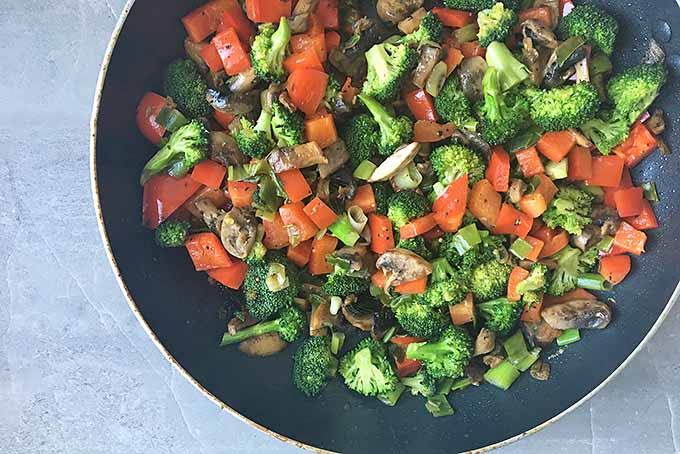 Horizontal image of a skillet with vegetables on a gray surface.