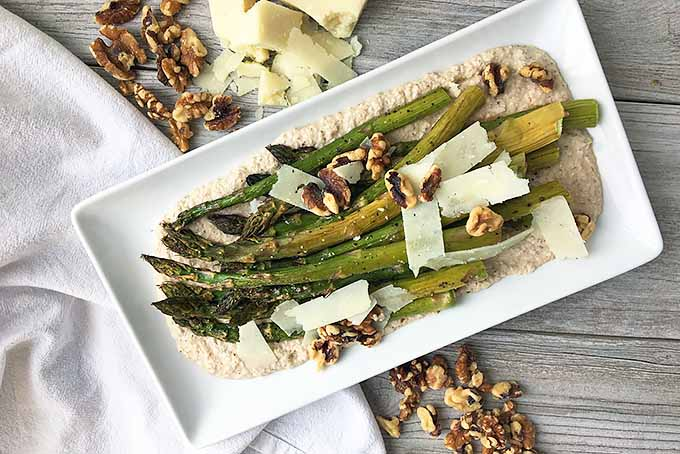 Horizontal top-down image of a plate of asparagus surrounded by nuts and cheese on a white towel with a fork on a gray wooden surface.