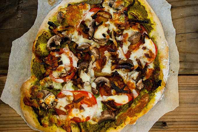 Top down view of a pizza made with pesto, mushrooms, and caramelized onions.