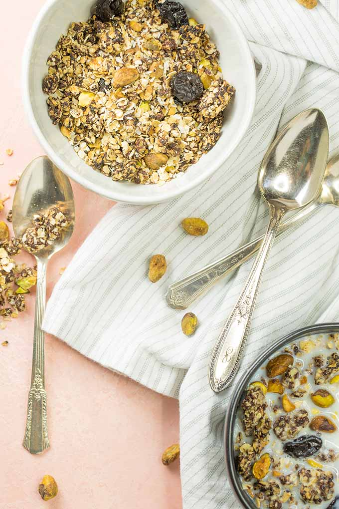 Bowls of granola cereal with milk and spoons.