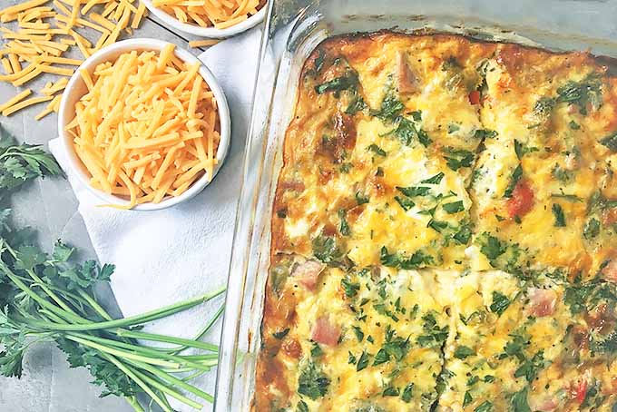 Horizontal image of a casserole in a glass dish with bowls of cheese and parsley on a white towel on a gray surface.