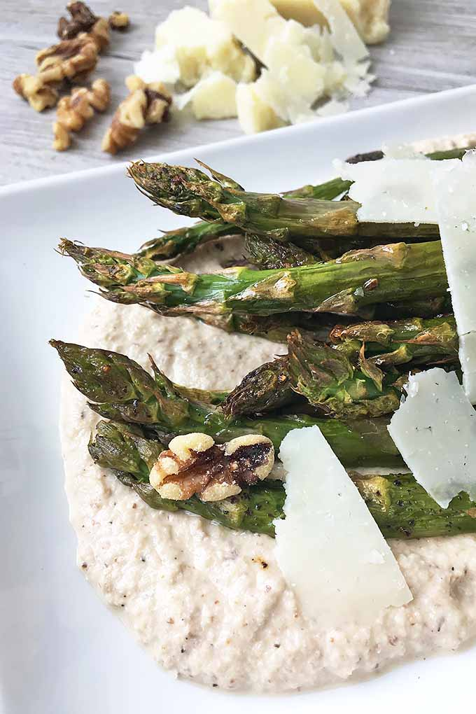 Vertical close-up image of a plate of asparagus with a tan sauce and nuts and cheese on a gray wooden surface.