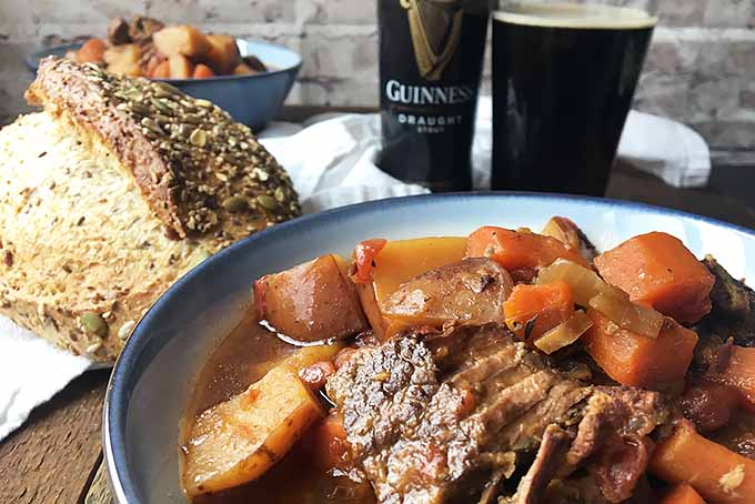 Horizontal closeup image of beef stew in a bowl, with bread, beer, and another bowl of stew in the background on a wooden surface with a white towel.