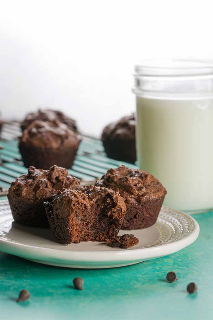 Vertical image of a glass of milk to the right of white plate of brownie bites with a bite taken out of one to show the inside, with more brownie bites on a wire cooling rack in the background, on top of a blue surface with a white wall in the background.