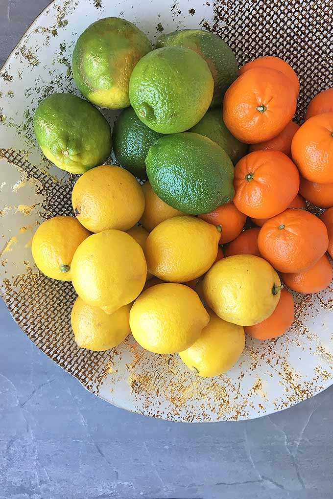 A display bowl with lemons, limes, and oranges.