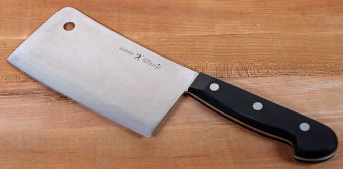 J.A. Henckels International Classic 6-Inch Light-Weight Meat Cleaver on a maple butcher block counter.