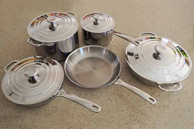 A collection of five pieces of stainless steel Le Creuset cookware, four of which have lids, on a beige countertop.