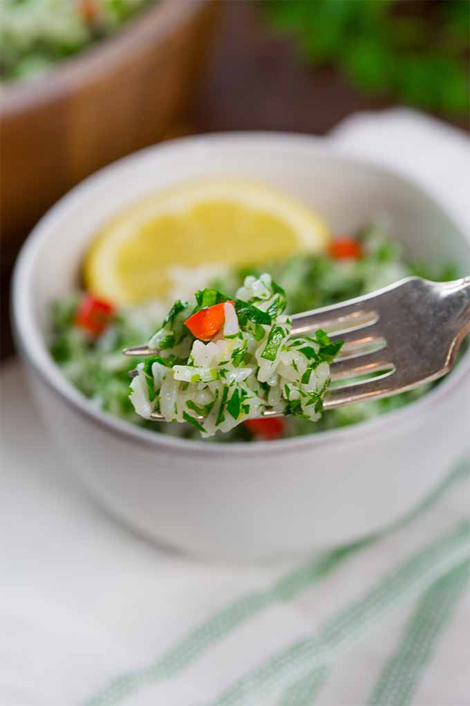 Vertical image of a forkful of rice salad with minced parsley and diced red pepper, with a white ceramic bowl filled with the salad and topped with a wedge of lemon in shallow focus in the background, on top of a brown wooden table with a pastel green-striped white kitchen towel spread on the table.