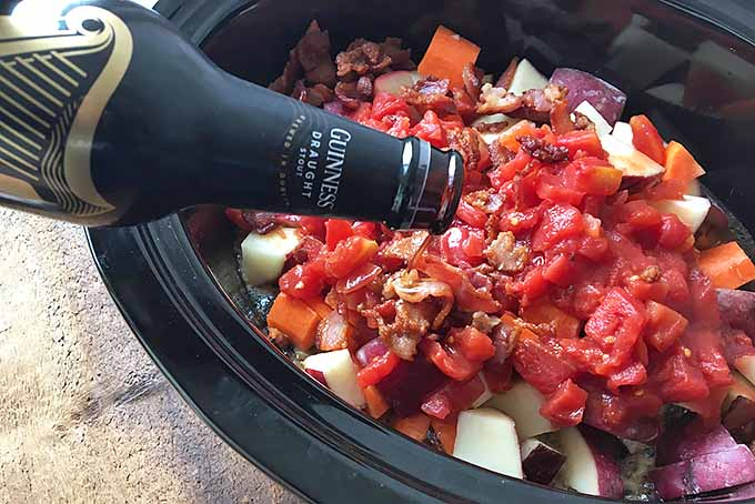 Horizontal image of a vegetables in a slow cooker pot, with beer being poured into it.