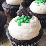 Square image of chocolate cupcakes with chocolate/green sprinkle garnishes on a cookie sheet.