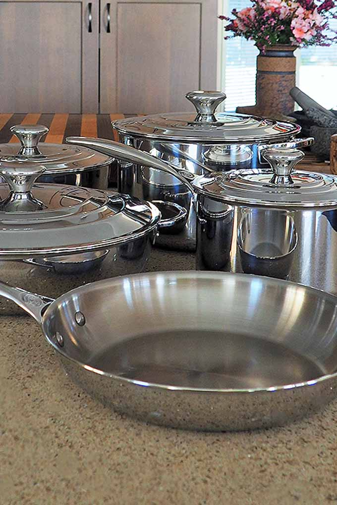 Vertical image of five pieces of stainless steel Le Creuset pots and pans, four with lids, on a kitchen countertop, with a vase of flowers and cabinet doors in the background.