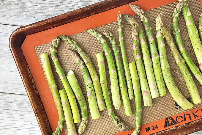 Horizontal image of asparagus spears on a baking pan lined with a silicone mat on a gray wooden surface.