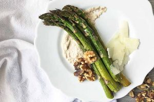 Horizontal image of a plate with asparagus, sauce, nuts, and cheese on a white towel.