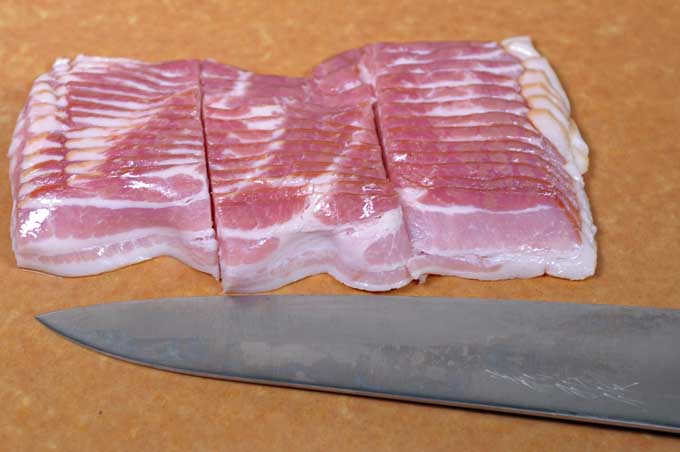 Center cut bacon being sliced into thirds with a Japanese Chef's knife.