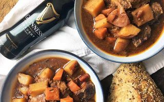 Horizontal image of bowls of beef stew on a white towel with beer and bread on a wooden surface.