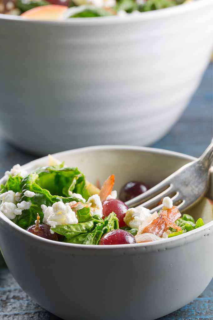 Vertical image of a white bowl of spinach salad with goat cheese, prosciutto, grapes, and apples with a fork stuck into the bowl, with a larger white bowl of salad in the background.