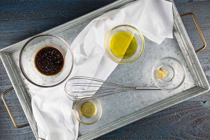 Top down view of ingredients for salad dressing measured own in small glass bowls on a metal tray topped with a white cloth, including mustard, oil, honey, balsamic vinegar, and oil, with a metal whisk, on a blue wooden background.