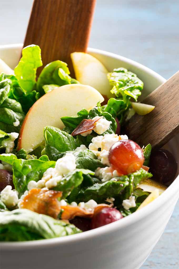 Closeup of a white bowl of spinach salad with apples, goat cheese, prosciutto, and pickled grapes, with wooden serving utensils.