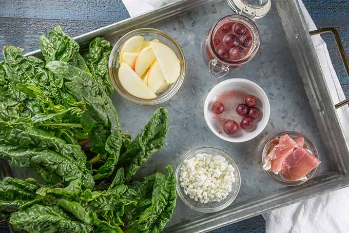Top down view of a metal tray topped with large leaves of fresh spinach, and small glass and white porcelain bowls and ramekins of sliced apple, crumbled goat cheese, pickled grapes, and strips of prosciutto.