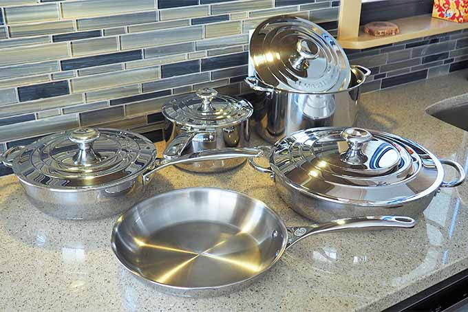A light beige kitchen countertop with blue and beige tile backsplash, with a variety of stainless steel cookware on the countertop.
