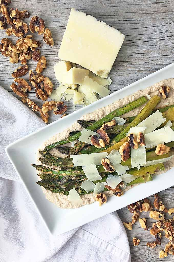 Vertical top-down image of a white plate of asparagus surrounded by walnuts, cheese, and a white towel on a gray wooden surface.
