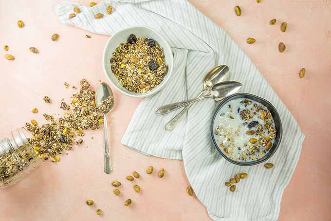 Bowls of granola with milk, spoons, pistachios, and a towel.
