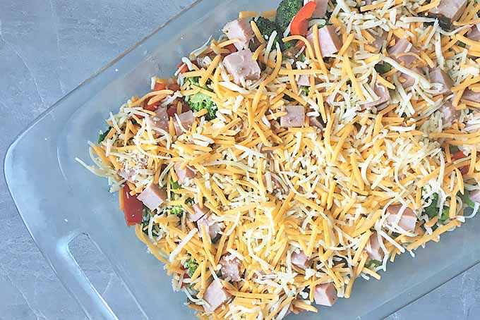 Horizontal image of vegetables, meat, and cheese in a glass baking dish on a gray surface.