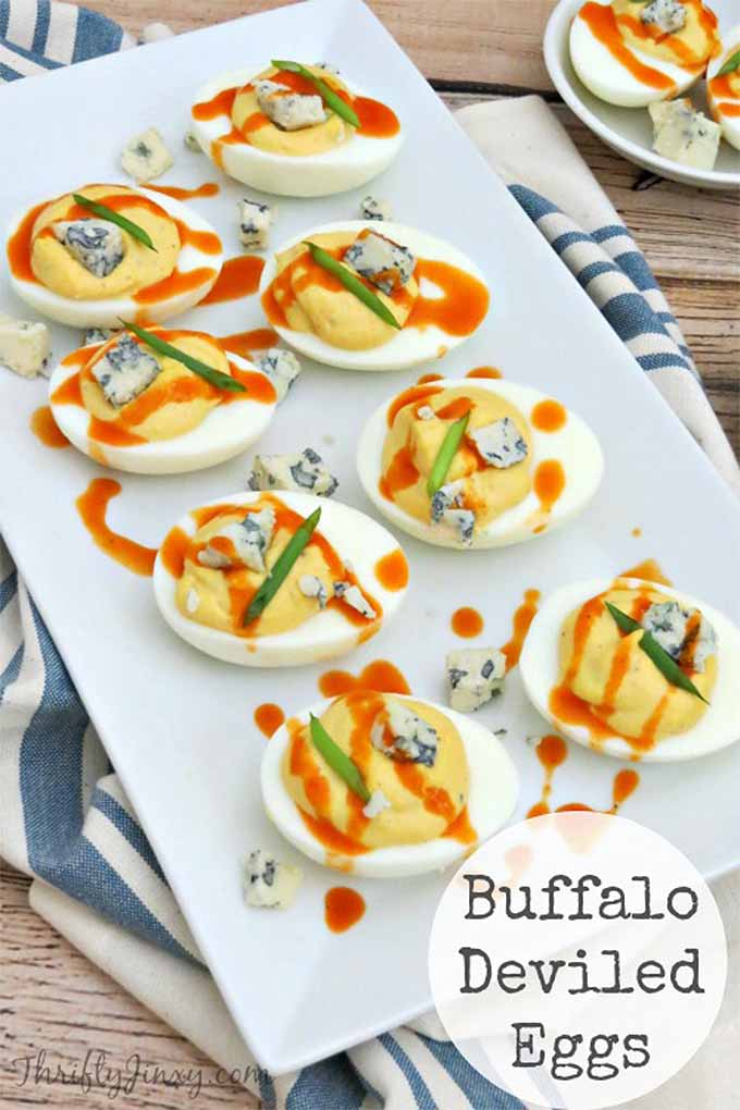 Vertical image of eight halved hard-boiled eggs filled with deviled yolks mixed with crumbled blue cheese, and topped with a drizzle of buffalo sauce, on a rectangular white ceramic plate atop a blue and white striped dish towel.