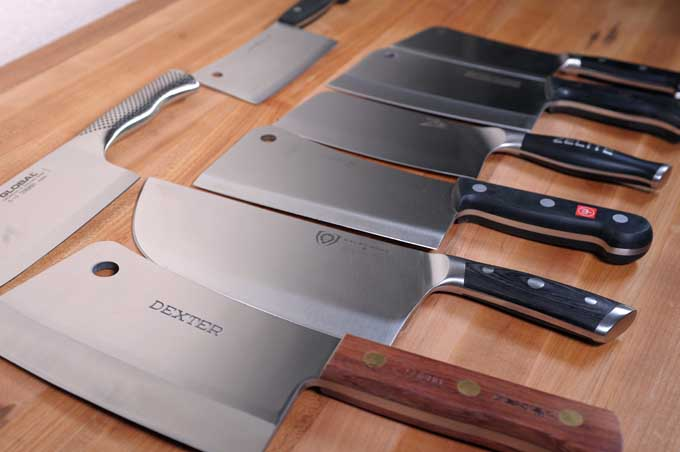 Oblique profile of eight different top rated meat cleavers on a wooden prep table.