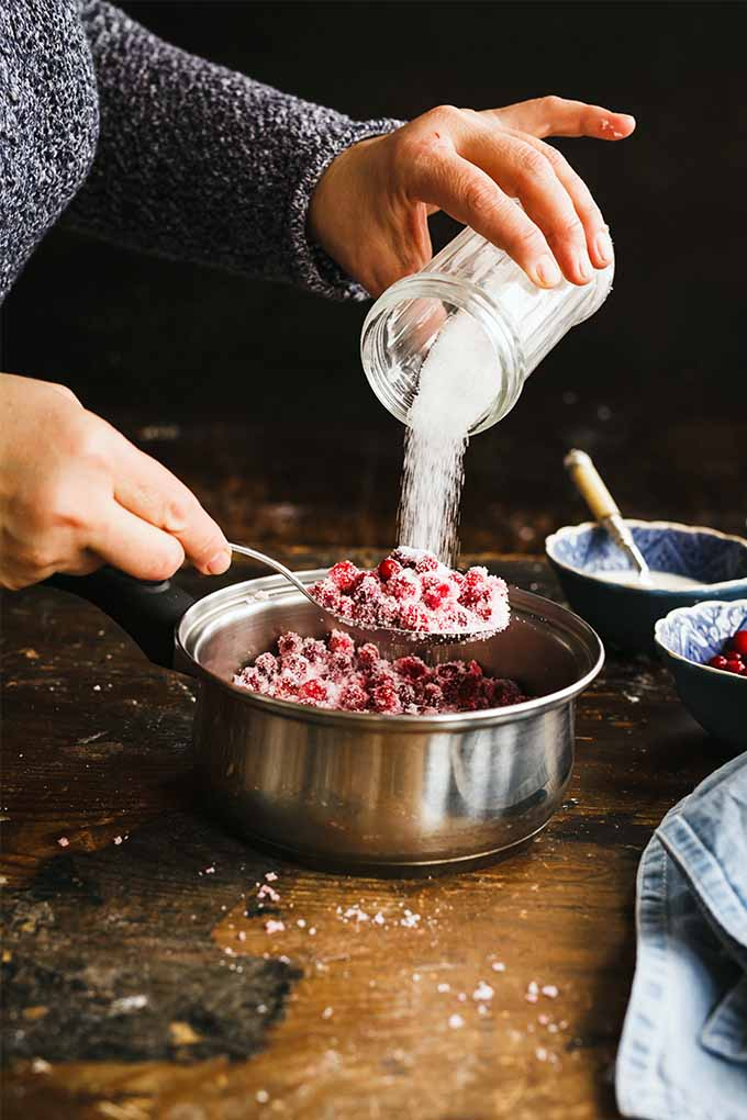 Vertical image of a woman's hands and arms clothes in a gray sweater, pouring a glass container of sugar into a saucepan full of red berries, on a brown countertop with bowls and various kitchen implements, with a black background.