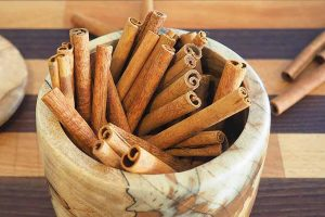 Mortar filled with cinnamon sticks on a wooden cutting board.