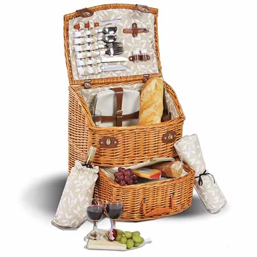 Wicker picnic basket with full service for two, including wine glasses, plates, cutlery, and napkins, isolated on a white background.