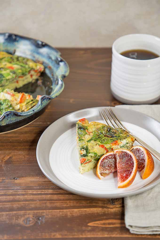 Vertical image of a slice of vegetable crustless quiche and three slices of ruby red grapefruit with a fork on a white plate, with a blue ceramic pie dish of quiche and a white mug of coffee in the background on a brown table.