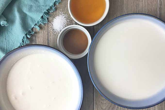 Horizontal image of bowls of milk, honey, and spice, with a pile of spice and a blue towel.