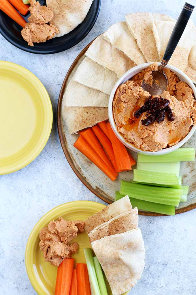 Vertical image with a top-down view of a platter of celery and carrot sticks and sliced pita bread with a bowl of sun-dried tomato hummus with a spoon stuck into it at the center of the platter, beside a yellow plate and a navy blue plate filled with the snacks, and an empty yellow plate, on a light gray background.
