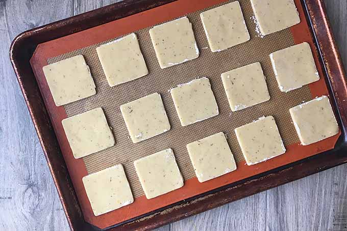 Horizontal image of square-shaped cookie dough on a baking sheet lined with a silicone mat.