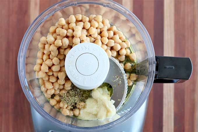 Top-down shot of hummus ingredients in the plastic canister of a KitchenAid food processor with a black handle and silver base, including chickpeas, roasted garlic paste, and dried oregano, on a striped wooden background.