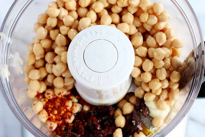 Top-down view of an open KitchenAid food processor canister filled with chickpeas, red pepper flakes, chopped sun-dried tomatoes, salt, garlic, lemon juice, and tahini.