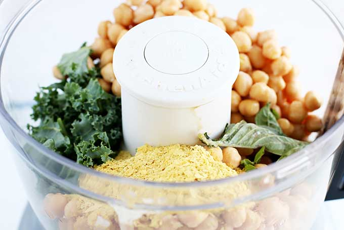 Horizontal image of ingredients for hummus in a food processor.