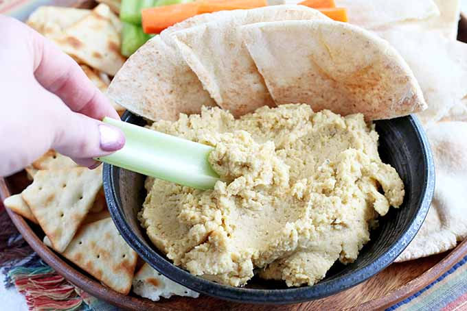 A woman's hand with pink painted fingernails dips a pale green celery stick into a bowl of hummus, with pita bread and chips, and sliced vegetables on a serving tray in the background.
